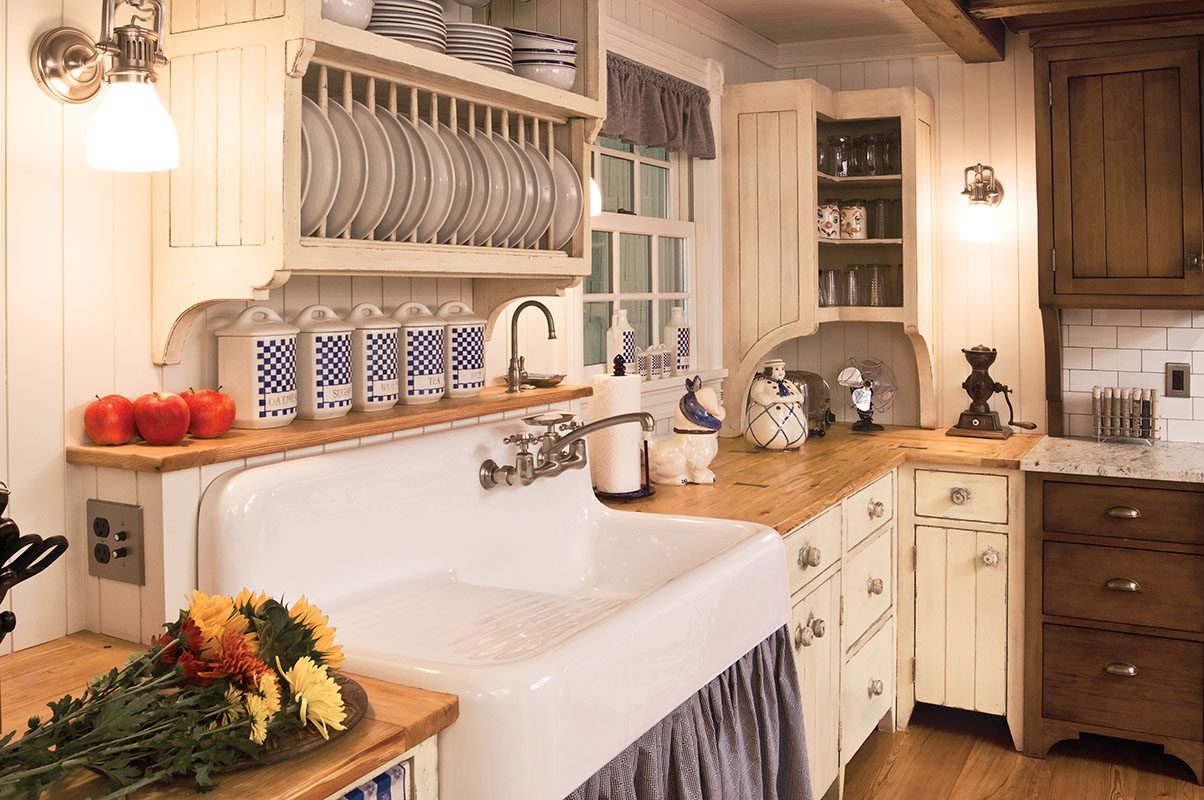 The kitchen was designed by Lauren Frye; custom finishes are by Guy DiMatteo of Artisan Finishing Services. A custom plate rack hangs above a period-style Kohler sink. A soft-pleated fabric skirt, fastened with Velcro, offers colorful coverage for the under-sink area.