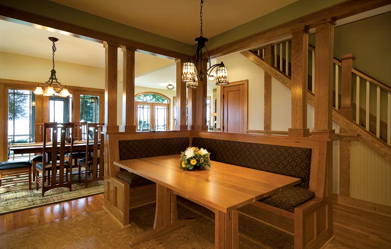 A built-in banquette offers space-saving dining. Clustered columns separate the kitchen, dining room, and hall while keeping the rooms open and airy.