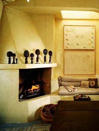 Kerrigan designed an adobe-style fireplace for the kitchen and finished the walls in a tea linen for an antique look.