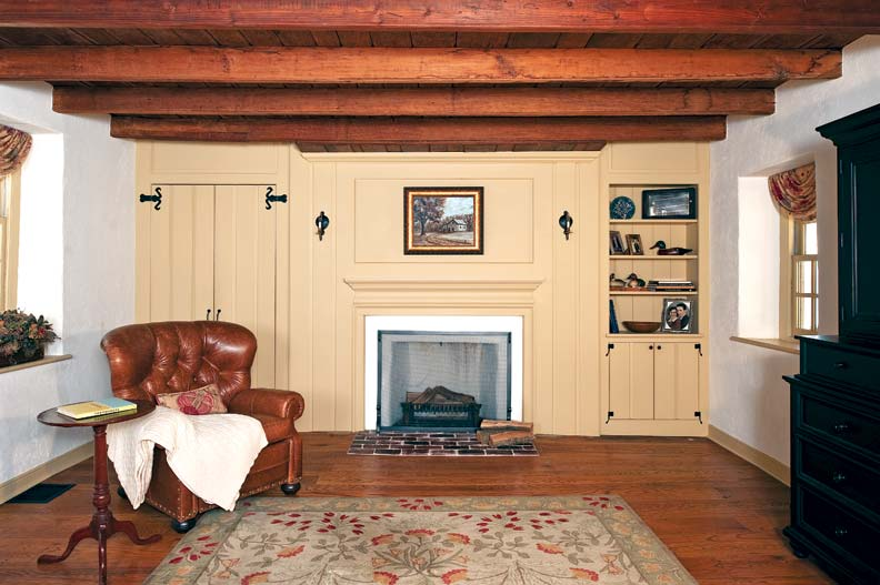 Kevin McGinnis removed unsympathetic paneling and created new fireplace walls. The door at left hides an office cubby with the family computer.