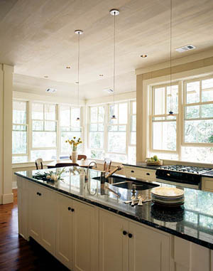 The ceiling is cypress wood finished in a cream-colored wash. The windows are grouped in threes and are left without window treatments to allow the natural light to filter through the space.