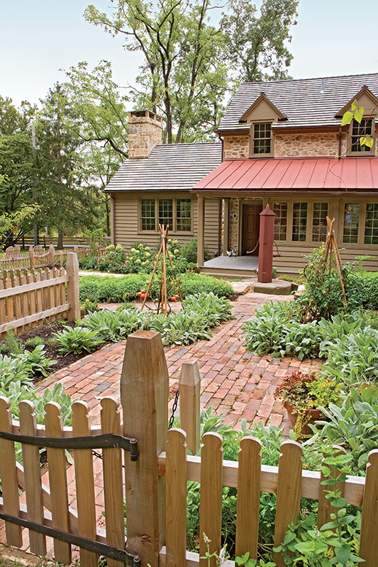 "The colonial era-inspired vegetable garden surrounds a red-brick courtyard; the fence has a historic local design. Roofs mix wood shingles, ceramic tiles, and seamed metal, giving the house a convincing ""assembled over time"" look."