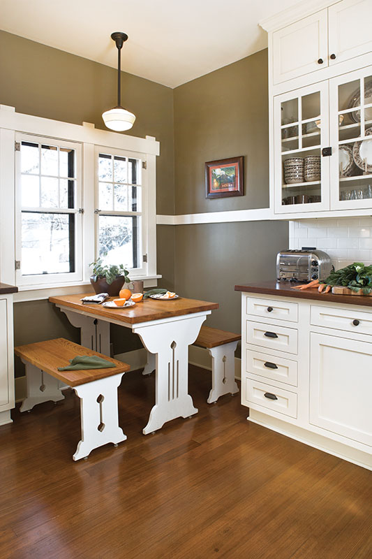 A breakfast table and benches made for the owners' previous 1918 bungalow were a perfect fit in the new kitchen; the original fir floor had been buried under several layers of vinyl flooring.