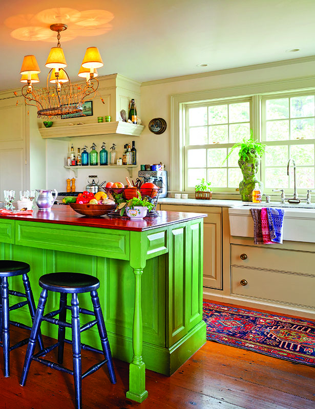 Simple and traditional, the painted cabinets recede into walls. The island was built like a farmhouse table and is finished with real milk paint. Open shelves over the range-top make this is a practical cook's kitchen. The apron-front sink echoes old-style basins.
