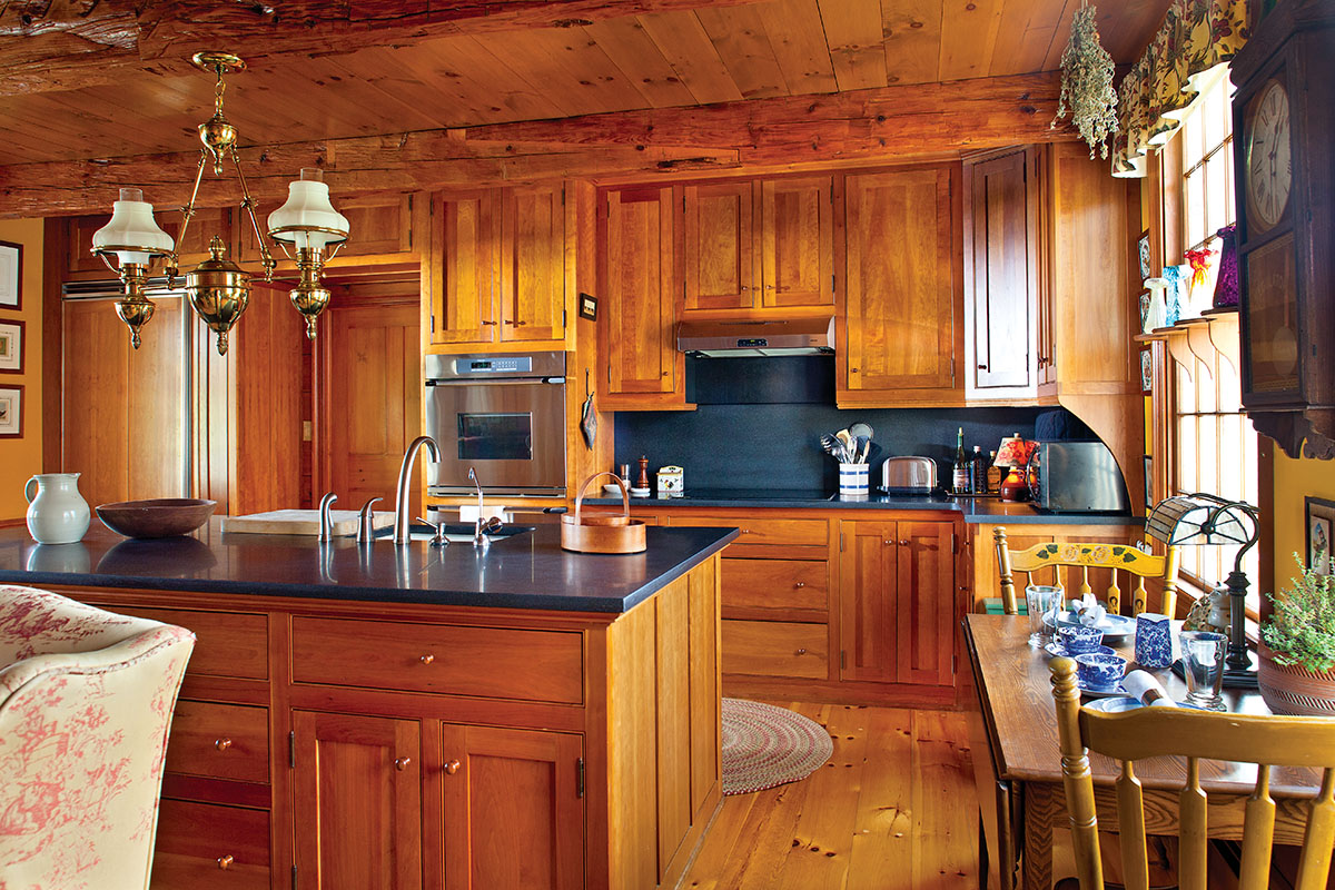 """The new kitchen is in a big old room that was, improbably, long used as a garage. It's 21' square and includes a fireplace, now restored. """"We made the fireplace part of the kitchen, creating a sitting area with a couple of wing chairs,"""" Larry Stanley says. The old floorboards had been irreparably stained and damaged, so the floors are new. Salvaged sections of old flooring have new life as the built-in cabinet in a corner next to the fireplace. The room is  simply furnished with mid-19th-century cabinets inspired by Shaker design. """"We chose cherry for the cabinets because it would age to the same color as the beautiful old beams, which are chestnut treated with tung oil,"""" Larry explains. Natural granite countertops with a soft, honed finish complete the look."""