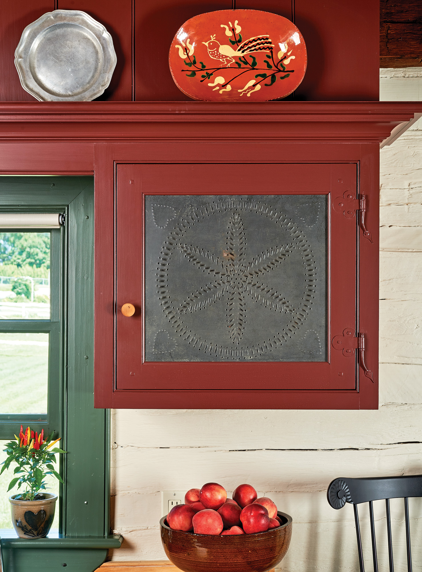 Contemporary cabinets are accented with a new pie-safe tin panel; redware and pewter platters are genuine reproductions.