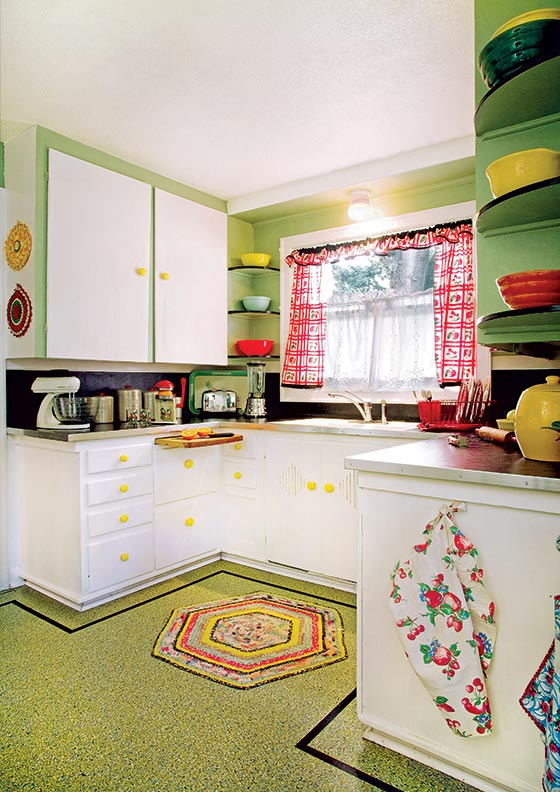 A linoleum floor with a confetti pattern and a simple border is a cheerful complement to this 1940s kitchen.