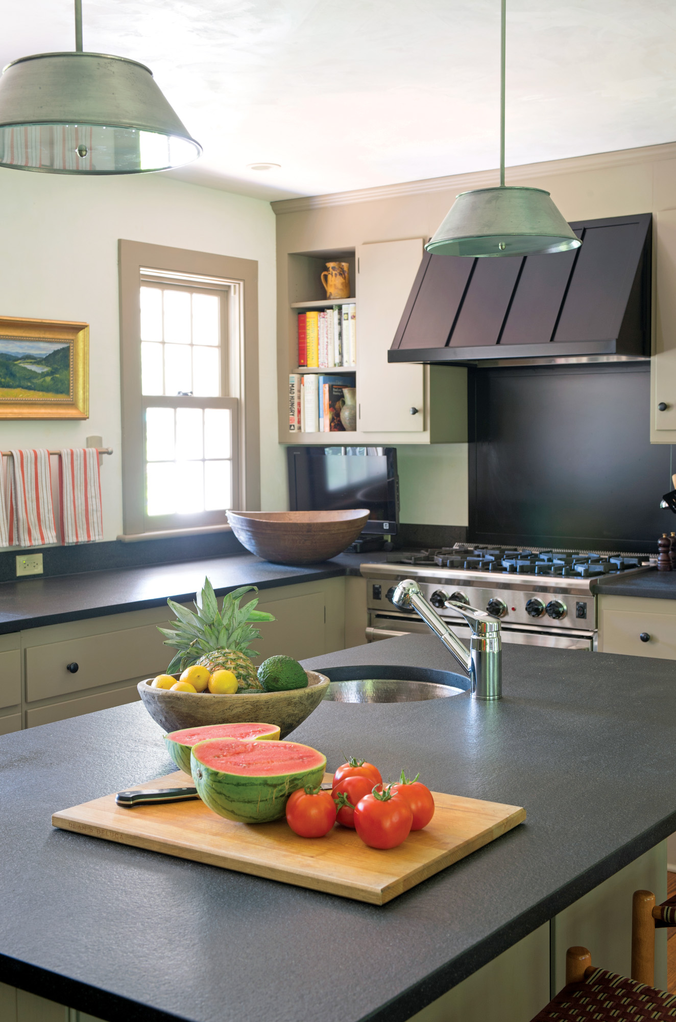The absence of wall-hung cabinets on the window wall is period- sensitive and opens up the room. The custom range hood (www.betlan.com) is standing-seam metal with a powder-coat finish. Custom hardware is wrought iron.