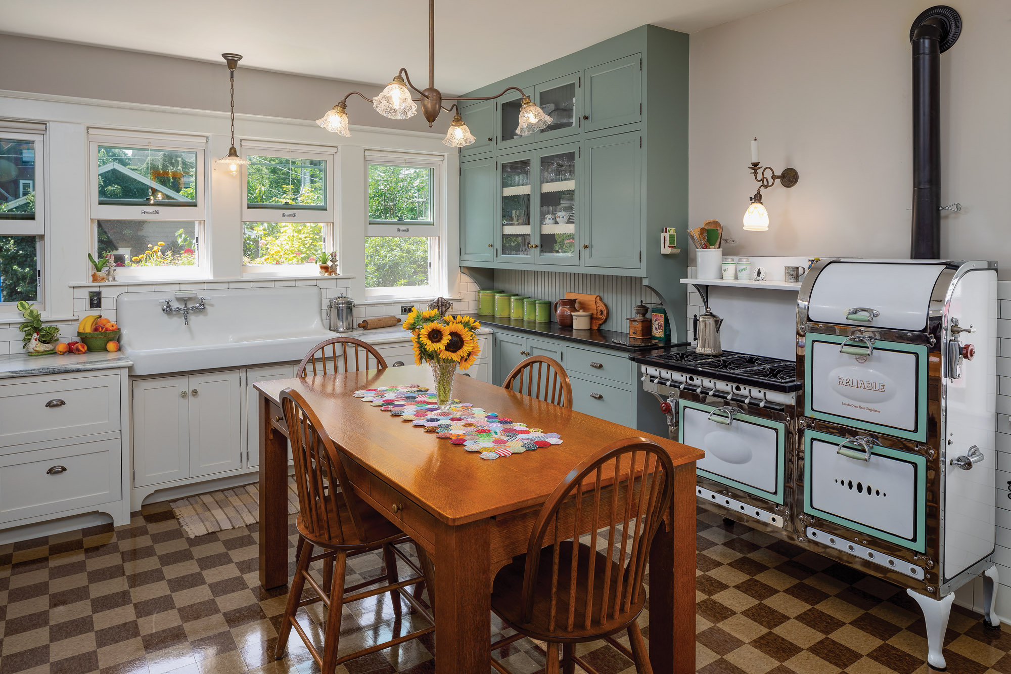 A brown checkerboard floor, antique appliances and lighting fixtures, painted cabinets, and a kitchen table create a convincing period kitchen.