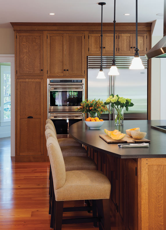 In this Craftsman-inspired kitchen by Crown Point, storage cabinets above appliances store items not used every day, such as party platters and seasonal dishes.
