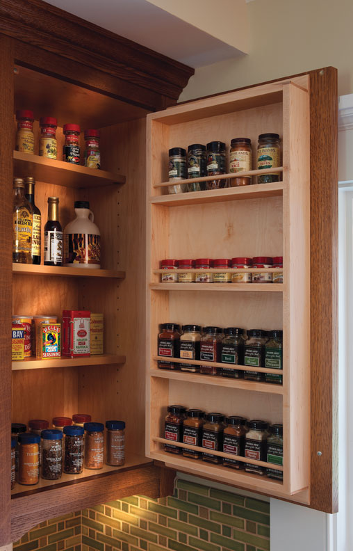 A custom-designed spice shelf sits next to the stove in the Craftsman kitchen.