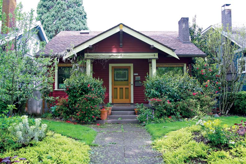 A perfect little Craftsman cottage has a large front-gabled entrance porch and the big, flower-filled yard characteristic of Ladd's Addition. Open timber-work, wide eaves, and picture windows elevate it into the Craftsman category.