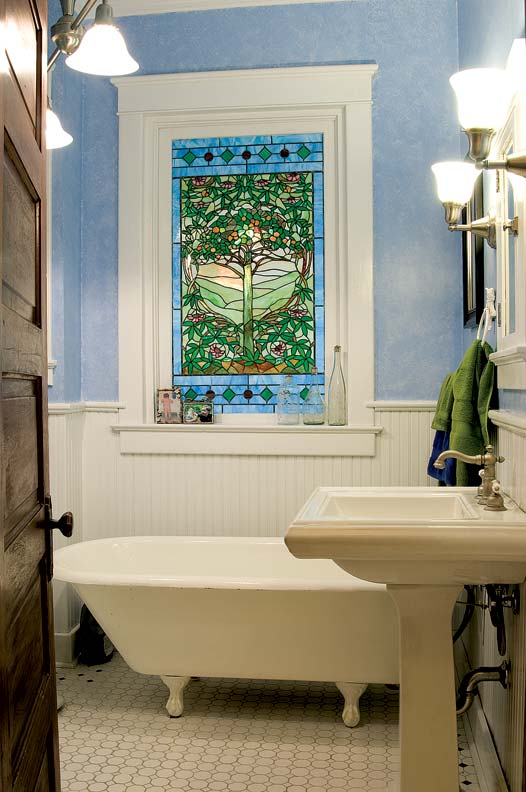 This stained glass window, bought at auction, provided incentive to restore the bathroom.