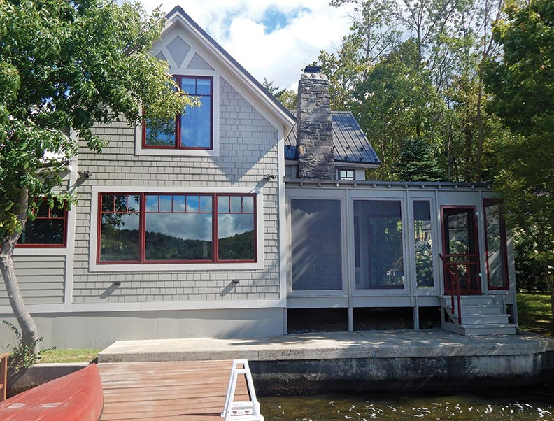 Built right on the lake, the old cottage (bottom) was badly rotted. Handsome windows and new fiber-cement siding (top) improved its looks.