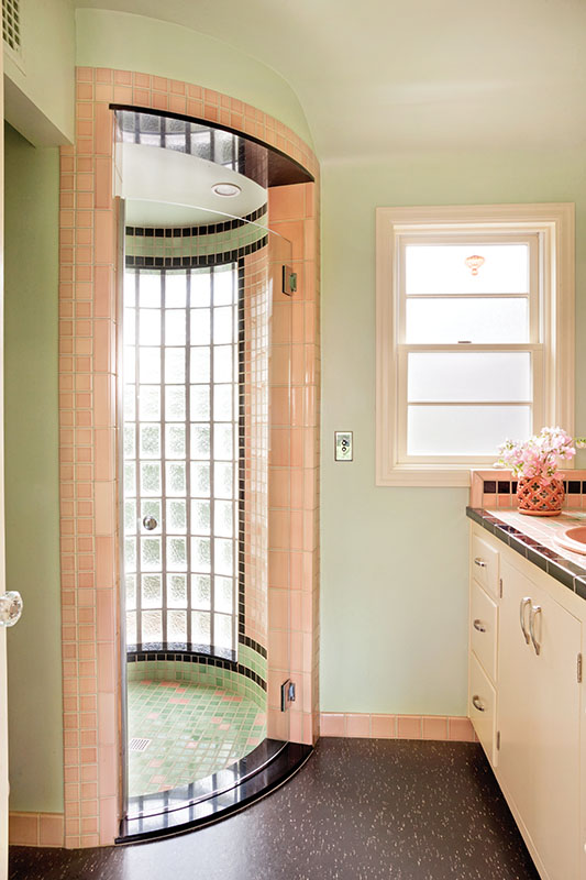 """Inspired by the showers in Portland builder Robert Rummer's mid-century homes, designer Matthew Roman suggested bent glass for the shower door, """"a splurge, but so worth it."""" In Art Deco fashion, pink, green, and black mosaic tiles line the circular walls. Glass block admits light. A tiled cubby is reminiscent of those pink 50s bathrooms."""