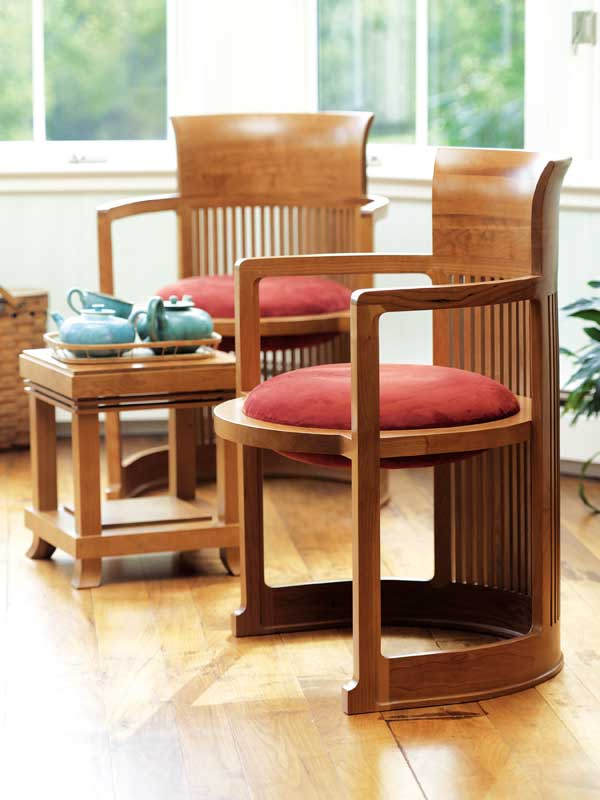 Licensed reproduction 'Barrel Chairs' by Copeland Furniture cozy up to the 'Robie Tabouret,' all Prairie pieces designed by Frank Lloyd Wright.