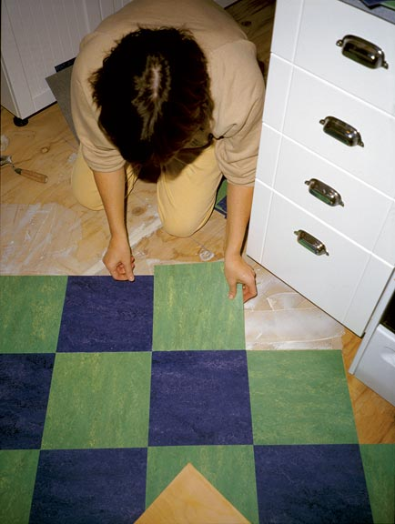 Carefully wiggling floor tiles as you place them helps seat them in the adhesive.