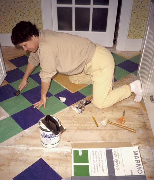 After carefully laying a field of tiles and hammering them in place, Lisa Jordan smooths seams with a wallpaper seam roller.