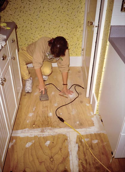 Wearing a protective mask, Lisa sands blemishes that were plugged with a polyester filler. The technique formed an almost perfect subfloor, but a few small seams eventually telegraphed through.