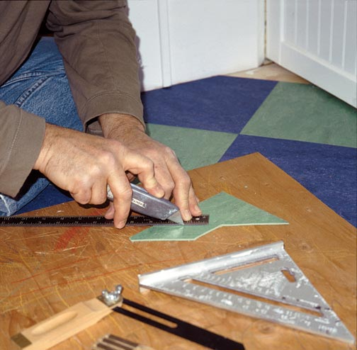 A few tools are all you need to cut the edges of linoleum tile. Using a razor knife, a straight edge, and a board as a work surface, the author trims a tile.