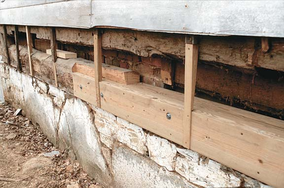 Bolting up a sill from lengths of pressure-treated lumber allowed th crew to remove and replace the old sill a section at a time without jacking the house. The vertical battens nailed to the logs carry the siding.