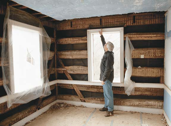 Stripped of its failed plaster, an upstairs bedroom lucidly reveals the skeleton of the Rohrbach House: massive horizontal oak logs joined at the corners in vertical posts. Doug Reed points to vestigial joist pockets, evidence of the earlier use for the timber.