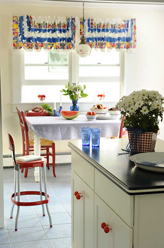 Maple cabinets got fresh white paint and red retro knobs; colorful mid-century wares give instant style to a kitchen where little renovation was done.