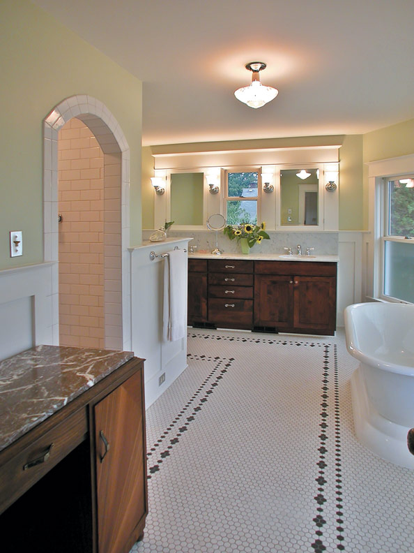 A hex tile floor patterned with a simple flower-and-dot border is a timely restoration choice for this 1912 Foursquare in Portland, Oregon, as is the separate shower stall of subway tiles with razor-thin grout.