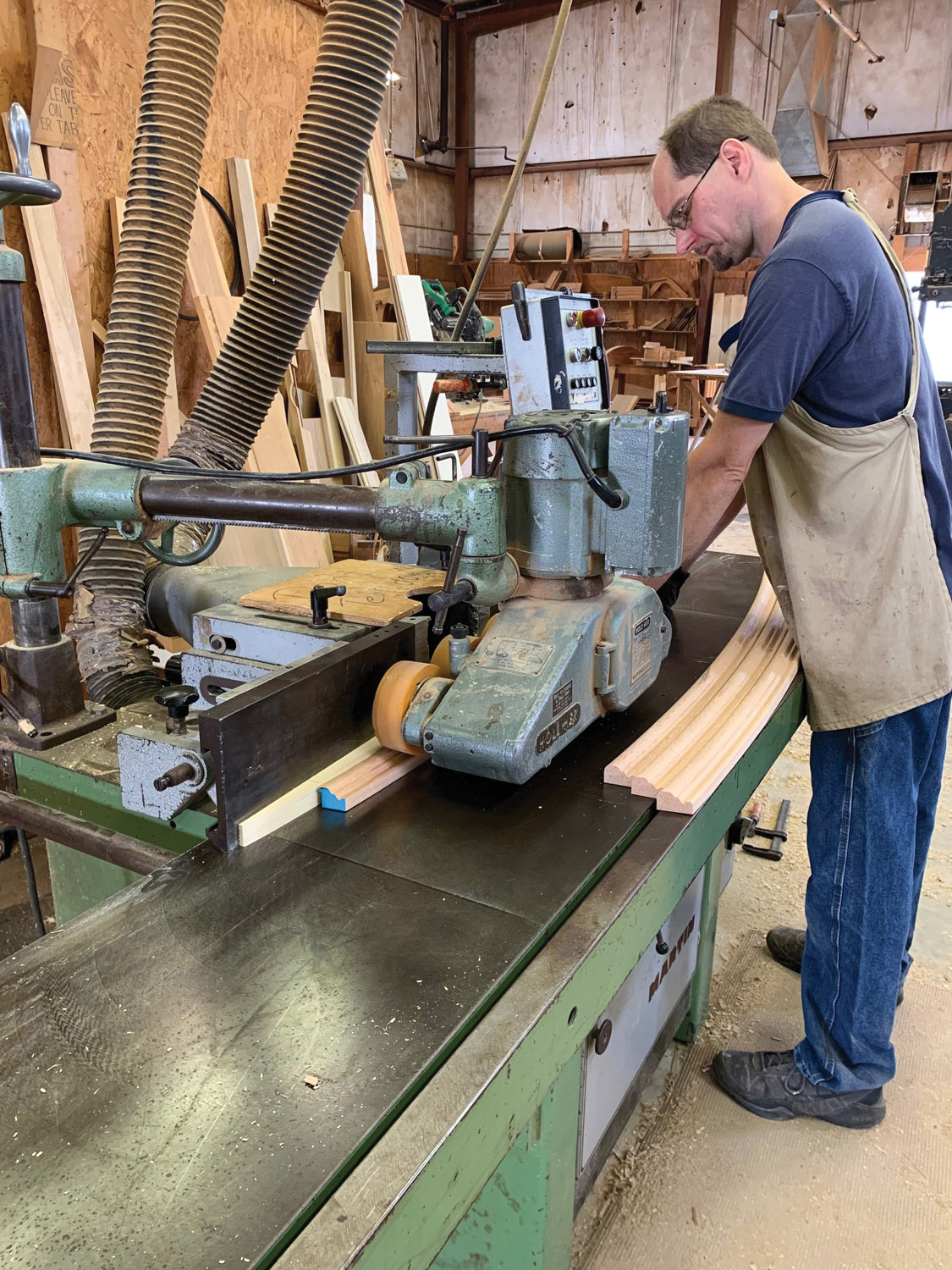 A workman  feeds wood into  the planer as  it cuts curved mouldings.