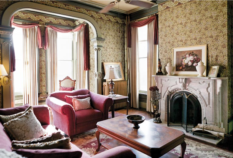 "William Morris-designed wallpapers (""Raspberry Bramble"" fill and an acanthus-leaf border) highlight the main parlor."