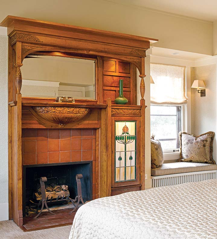 In the same house, a bedroom mantelpiece is softly and subtly lit by hidden rope lights behind the wood apron. The art-glass panel, original to this vintage mantelpiece, has also been backlit. A simple sconce provides light to read by.