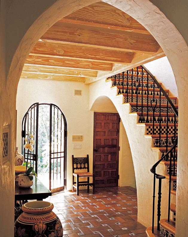 The front hall floors of Casa de la Torre are tiled in a traditional basketweave pattern. The wrought iron doors were salvaged from the Santa Barbara Biltmore Hotel.