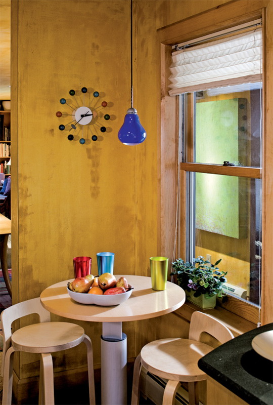 """A ca. 1960 George Nelson wall clock keeps the time above the breakfast table, lit by a prototype """"Ben"""" series Resolute Lighting pendant designed by Douglas Varey. The custom table is set with a pair of two K65 stools by Alvar Aalto."""