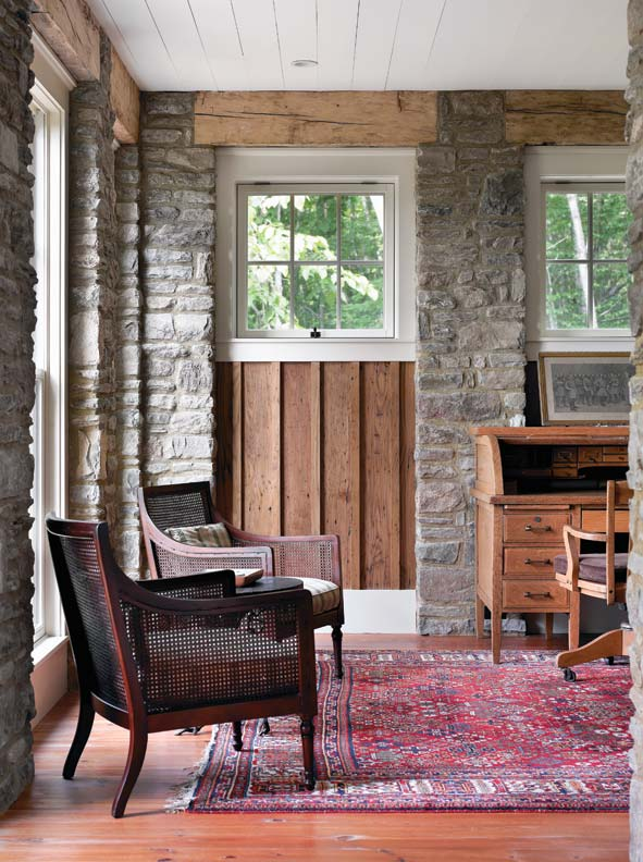 """Perimeter stone walls, rising from floor to ceiling in the interior, suggest """"foundation pillars."""" The lower level of the home is the more casual space for the homeowners and guests."""
