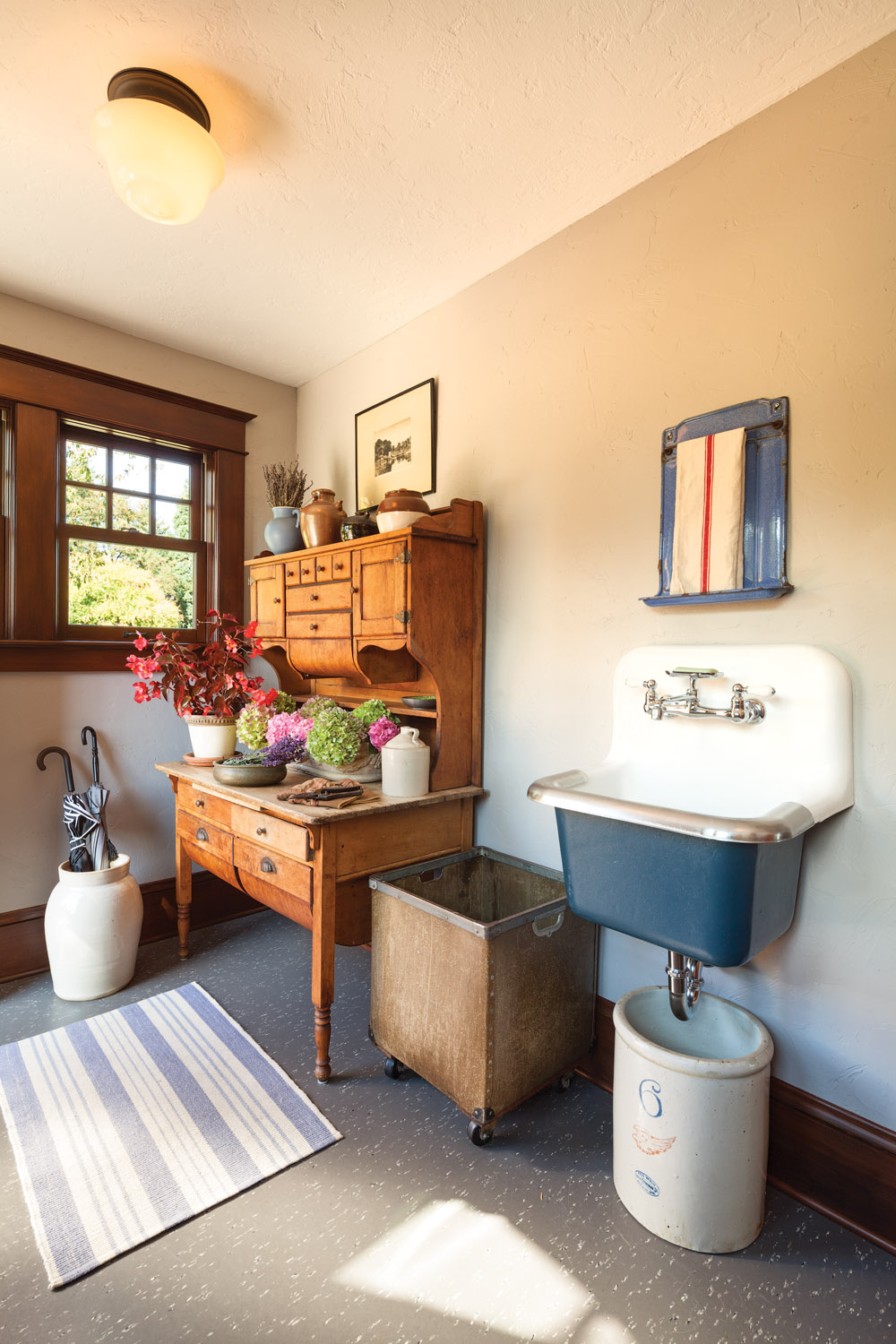 The original mudroom in a rural bungalow is again functional with the addition of an antique baker's cabinet and a vintage sink.