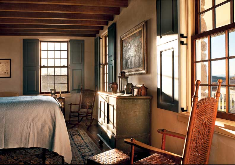 The guest bedroom is designed with colonial-inspired touches, such as interior shutters and country furnishings.