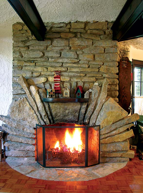 This massive fireplace is the centerpiece of one of Young's Boulder Park homes. To soften the sharp angles of the stones, the main body of the fireplace is constructed in a semicircular shape.
