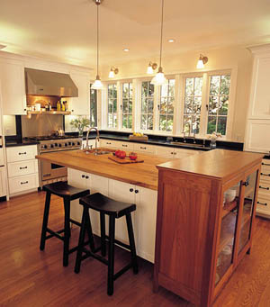 The kitchen cabinetry is painted a creamy white to contrast with the oak floors.