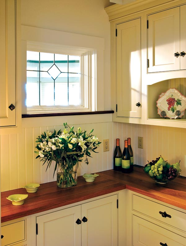 A window above the counters allows for additonal light into a small pantry designed by Crown Point.