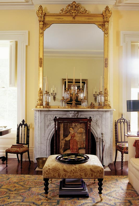A restored Renaissance Revival mirror sits atop the marble fireplace in the living room.