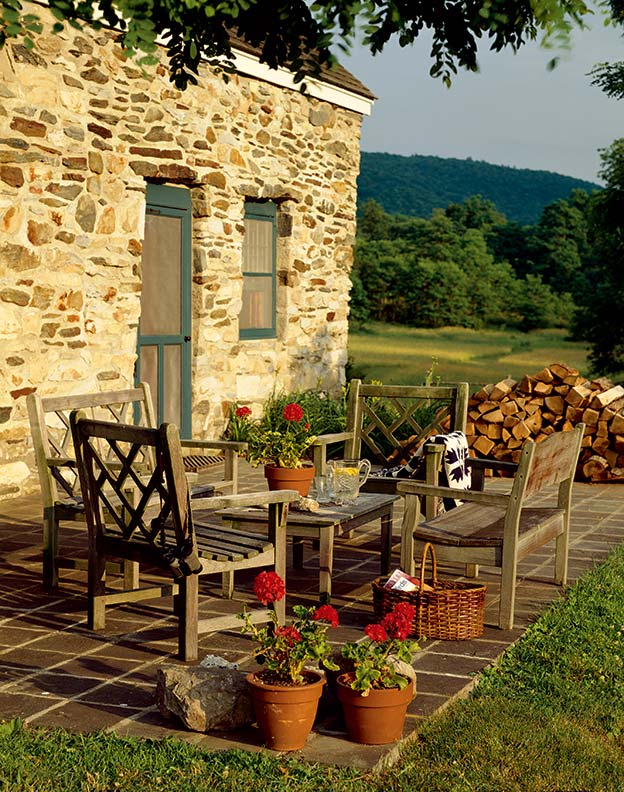 The spare stone terrace provides a spot to enjoy the meadow view.