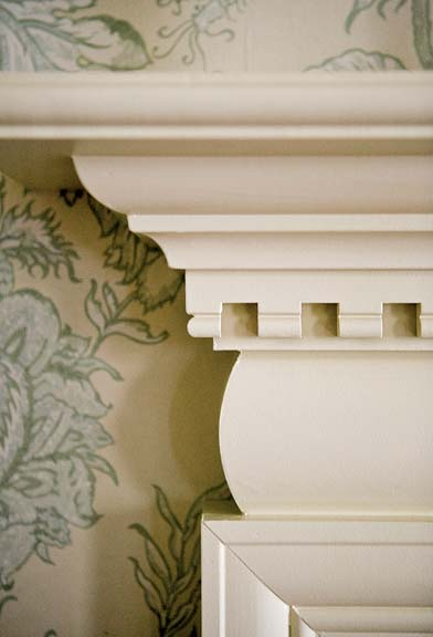 Architect Sally Weston designed a convex curve topped with dentil molding for a fireplace surround.