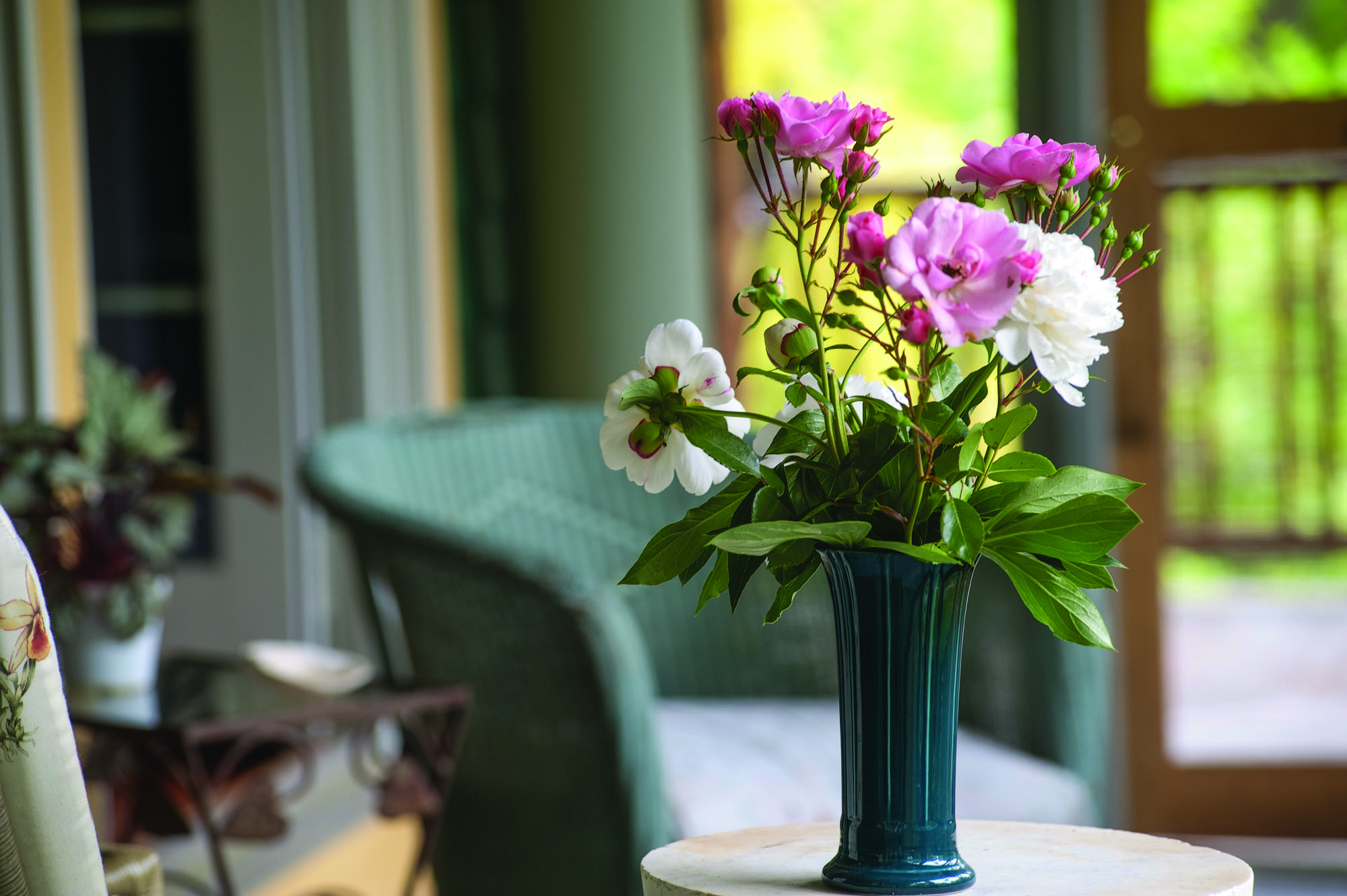 'Bonica' roses join up with herbaceous peonies to create an impromptu bouquet in a vintage Fiesta vase, on the porch.