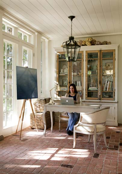Brooke works in her office space, where antiqued brick and beadboard ceiling add a layer of authenticity to the beach house.
