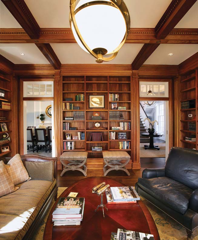 Off the entry hall, a study offers built-in shelving and a coffered ceiling.