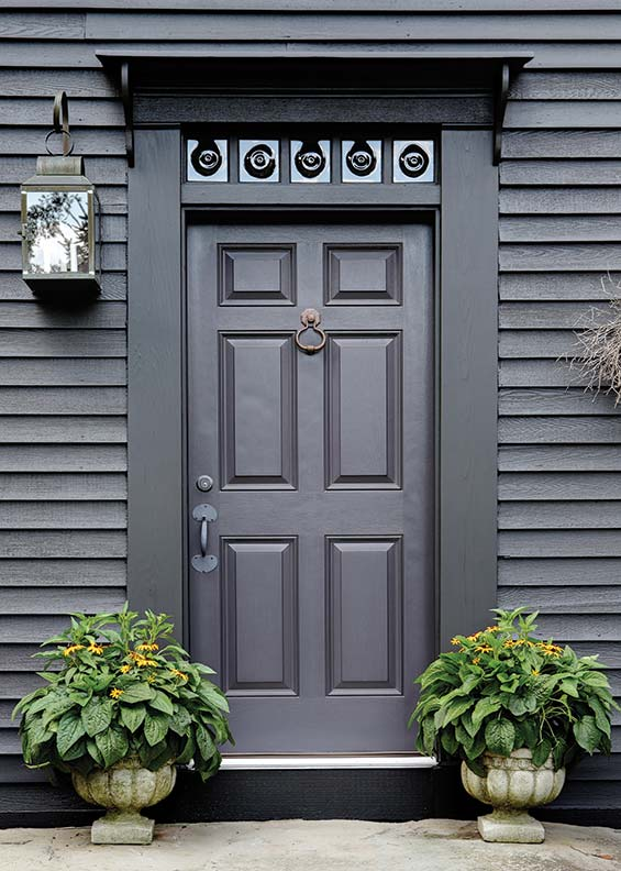 A six-panel door on a colonial-era house is topped with a transom of bullseye glass.