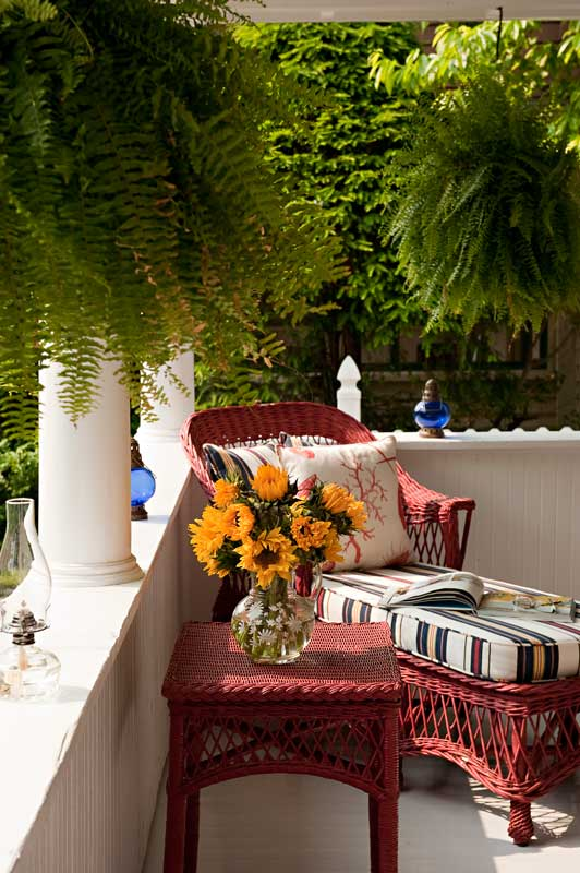 Old-fashioned Bar Harbor-style wicker furniture is painted in Benjamin Moore's 'Heritage Red'. Blue-and-white cushions wear 'Beach Stripe' by Ralph Lauren; pillows are covered in 'Vortice' and 'La Mer' from Clarence House.
