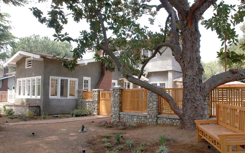 A new fence with open panels of unpainted wood and stone posts complements the natural materials in an Arts & Crafts bungalow.