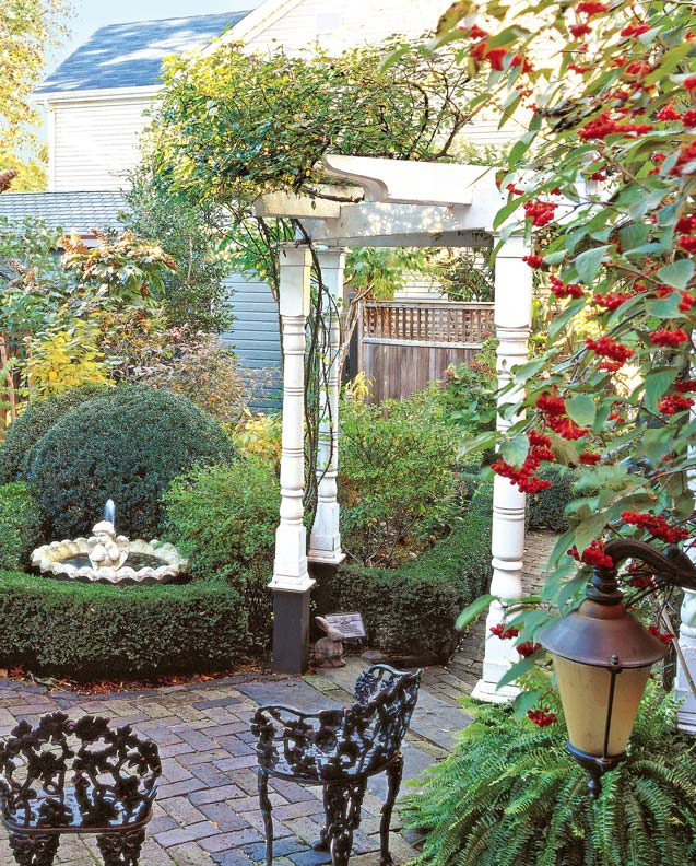 Turned posts add Victorian detail to a pergola in the garden of an 1887 Queen Anne.