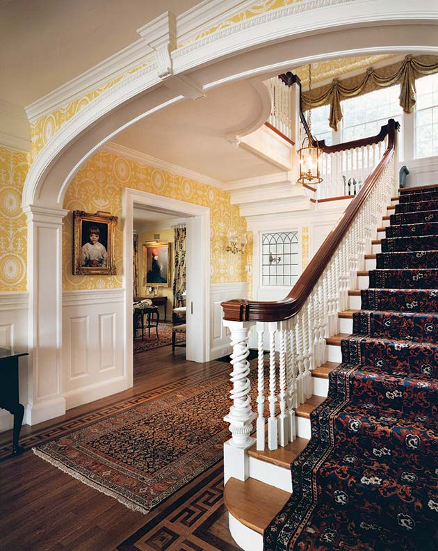 A quintessential colonial revival entrance hall is complete with a raised-panel wainscot and bold moldings.